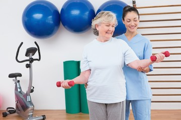 Therapist helping senior woman fit dumbbells