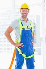 Construction worker wearing safety harness in office