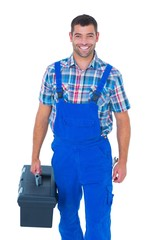 Happy handyman in coveralls carrying toolbox