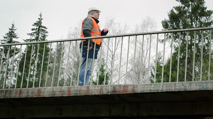 Engineer looks at his watch on the bridge