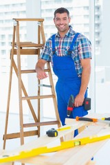 Carpenter with power drill standing by ladder