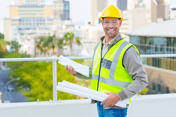 Smiling male architect with blueprints and clipboard