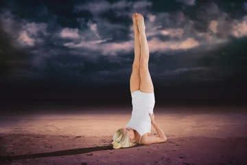 Composite image of fit young woman doing the shoulder stand pose