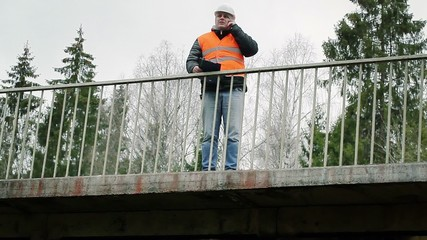 Engineer talking on the cell phone on the bridge