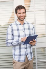 Happy man smiling at camera holding tablet