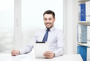 smiling businessman with tablet pc and documents