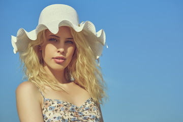 Beautiful lady with white wavy brim sun hat over blue sky