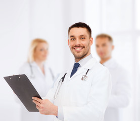 smiling male doctor with clipboard and stethoscope