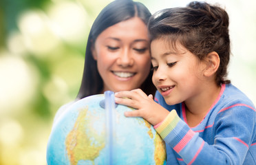 happy mother and daughter with globe