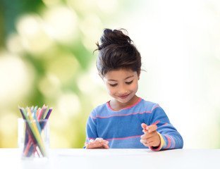 happy little girl drawing with coloring pencils