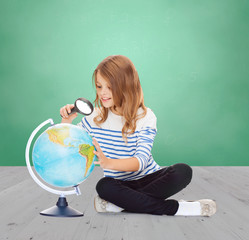 happy girl looking at globe with magnifier
