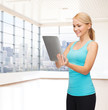 smiling woman with tablet pc in gym