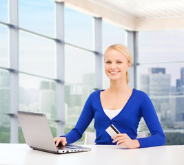happy businesswoman with laptop and credit card