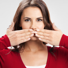 Young woman covering mouth, on grey