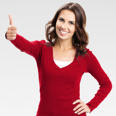 Woman showing thumbs up gesture, over grey