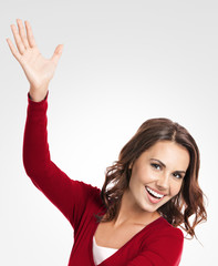 Cheerful gesturing young woman, showing something, on grey