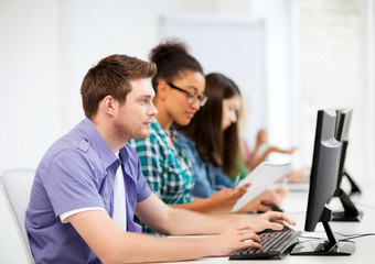 students with computers studying at school