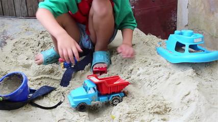 boy in sand with machine