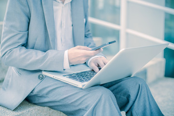 Businessman using laptop pc and mobile phone. He is sitting on a