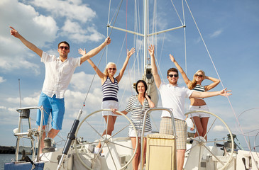 smiling friends sitting on yacht deck and greeting