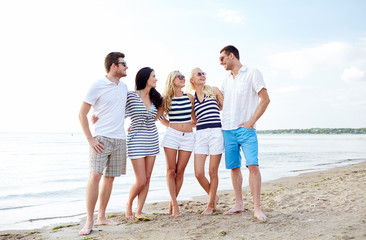 smiling friends in sunglasses talking on beach