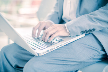 Businessman using laptop pc. He is sitting on a stairs.