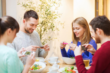 friends with smartphones taking picture of food