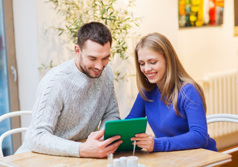 happy couple with tablet pc at cafe