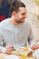 happy young man having dinner at restaurant