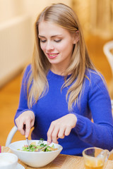 happy young woman having dinner at restaurant