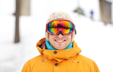 happy young man in ski goggles outdoors