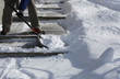 Man shoveling the show on  bright winter day - 78842342