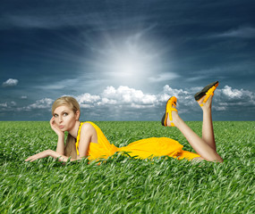 Blonde in yellow dress in green grass