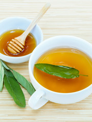 A cup of sage tea with fresh sage and honey.