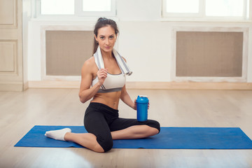 Beautiful athletic sporty woman sitting on yoga mat after some