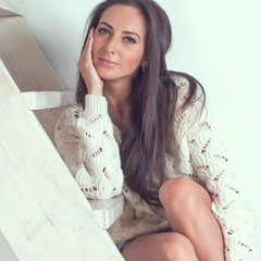 Caucasian dark-haired woman is sitting at the stairs in cozy