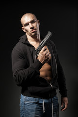 male gangster holding a gun isolated on dark background