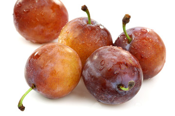 five fresh ripe plums on a white background