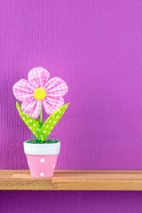 An artificial potted plant on a shelf with copy space background