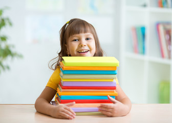 Happy little girl with a stack of books