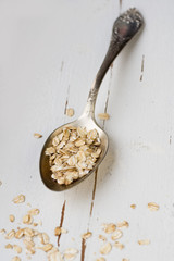 One tablespoon of oatmeal is a white wooden background