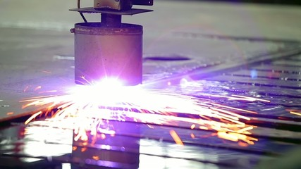 An industrial laser or plasma is cutting a steel metal sheet