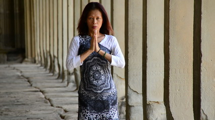 Female Buddhist with Hands in Prayer in Temple Hallway  - Angkor Wat Temple Cambodia