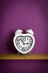 A heart shaped clock on a shelf with purple background