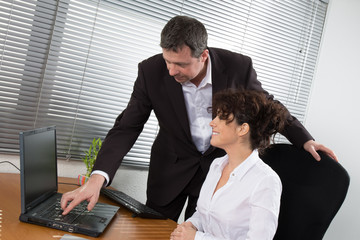 Man and woman, office workers in front of desktop computer