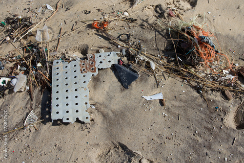 Lot of rubbish washed up on the shore on the beach - 78847520
