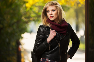 Young fashion blond woman in leather jacket in autumn park