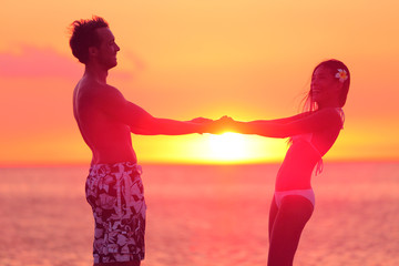 Romantic lovers couple dancing in bikini at beach
