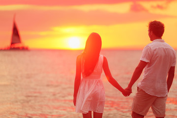 Couple holding hands together at beach sunset