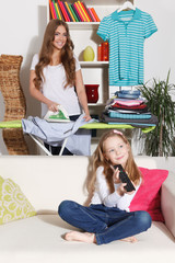 Woman ironing while child is watching TV